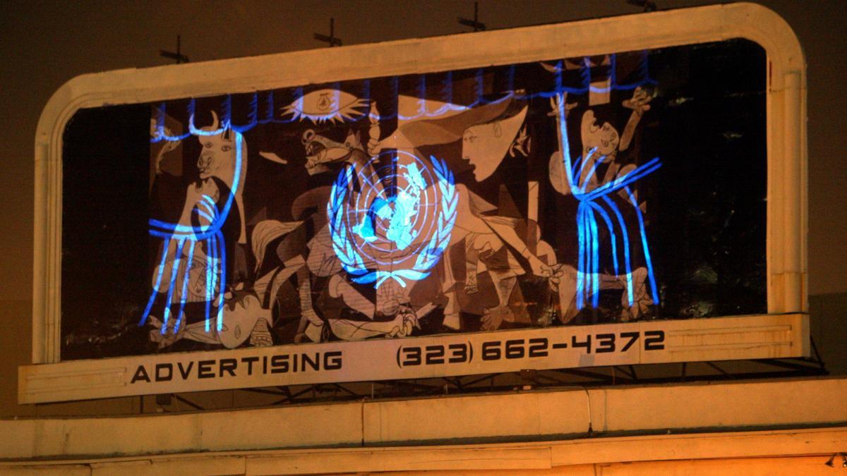 Réplica de Guernica con el logotipo de la ONU proyectado en la intersección de Hollywood and Sunset Boulevard